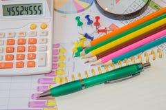 本文绘了五颜六色的图表 在谎言上笔、铅笔、笔记本和计算器 免版税图库摄影
