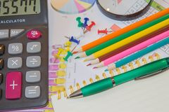 本文绘了五颜六色的图表 在谎言上笔、铅笔、笔记本和计算器 库存照片