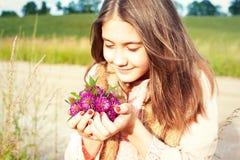 本质秀丽 年轻美丽的女孩嗅到的草甸三叶草fl 图库摄影