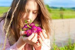 本质秀丽 年轻美丽的女孩嗅到的草甸三叶草fl 库存图片