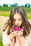 本质秀丽 微笑的女孩嗅到的草甸三叶草流程 免版税库存照片