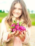 本质秀丽 拿着草甸三叶草flowe的微笑的女孩 免版税库存图片