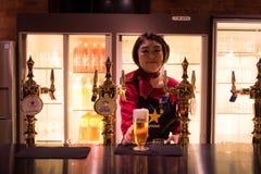 札幌,日本- 2016年5月05日:女服务员服务在札幌啤酒musuem的啤酒在札幌,北海道,日本 免版税库存照片