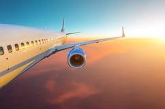 机体、翼引擎和尾巴的看法 在日落期间,飞机在飞行水平面上飞行 免版税库存图片