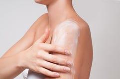机体关心英尺健康温泉水妇女 妇女对她的应用化妆奶油的肩膀关心 免版税库存照片