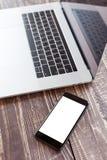 机动性和膝上型计算机在木书桌选择聚焦在电话白色bl 免版税库存照片