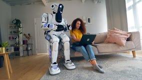 机器人、靠机械装置维持生命的人和人的概念 一个女孩和靠机械装置维持生命的人与一台膝上型计算机一起使用在屋子里 影视素材
