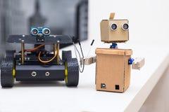 机器人保留导线并且在一张白色桌上的另一个机器人旁边站立 免版税库存照片
