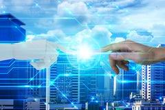 机器人和人的手有接触的在城市背景,人工智能和技术生态概念 免版税图库摄影