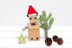 机器人在他的手上拿着冷杉小树枝和一个新年` s玩具 库存照片