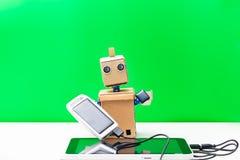 机器人在它的手上拿着一个太阳能电池 绿色背景 库存照片