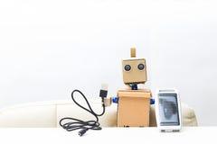机器人在手中拿着一个太阳能电池,导线 白色背景; 图库摄影