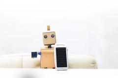 机器人在他的手上坐在桌上并且拿着太阳面团 库存照片