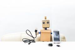 机器人在他的手上坐在桌上并且拿着太阳面团 免版税库存图片