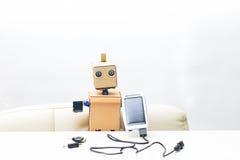 机器人坐在桌上并且拿着在白色b的两个太阳能电池 免版税库存图片