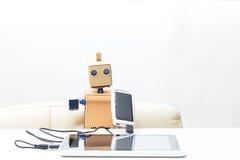 机器人坐在桌上并且拿着有导线的一个太阳能电池 免版税库存照片
