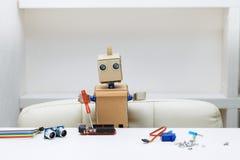 机器人坐在桌上并且拿着说谎在ro旁边的螺丝刀 免版税图库摄影
