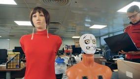 机器人头和女性时装模特移动他们的嘴在专家的控制下 股票视频