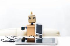 机器人拿着一个太阳能电池被连接到片剂 免版税库存图片