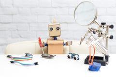 机器人拿着一把螺丝刀并且收集微型电路 Nea 免版税库存照片