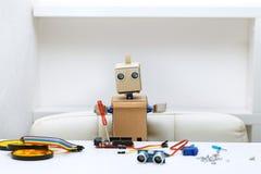机器人拿着一把螺丝刀,其次是聚集的零件 库存图片