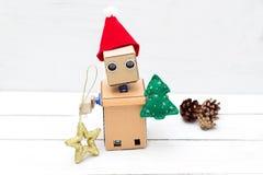 机器人拿着一棵圣诞树和一个圣诞树玩具 免版税库存图片