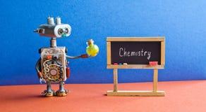 机器人有一个黄色化工试剂瓶的实验员 明亮的蓝色红色内部教室,词化学 免版税库存照片