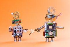 机器人爱情小说概念 滑稽的电路插口戏弄与电灯泡和心脏标志 逗人喜爱的面孔,蓝色红色注视玻璃 免版税库存图片