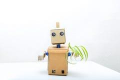 机器人用在桌和拿着上一朵绿色花的手在他的 图库摄影