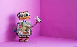 机器人电工在他的手上拿着一个电灯泡 创造性的在桃红色背景的设计futuric机器人玩具 复制空间 免版税库存照片