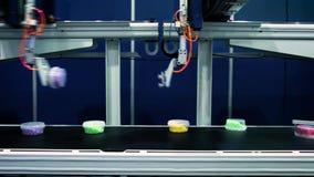 机器人的机械臂在食物生产传动机运转 适合箱子用在传送带的食物 股票录像
