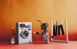 机器人自动化洗衣房 银色洗衣机,人` s牛仔裤裤子在与晒衣夹的晒衣绳烘干了 年龄 免版税图库摄影