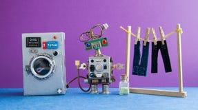 机器人自动化洗衣房 银色洗衣机,人` s牛仔裤裤子在与晒衣夹的晒衣绳烘干了 紫罗兰色 库存照片