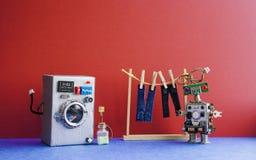 机器人自动化洗衣房 银色洗衣机,人` s牛仔裤裤子在与晒衣夹的晒衣绳烘干了 红色墙壁 免版税库存图片