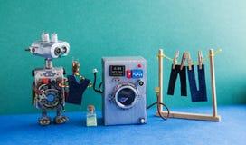 机器人自动化洗衣房 银色洗衣机,人` s牛仔裤裤子在与晒衣夹的晒衣绳烘干了 绿色 免版税库存图片
