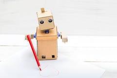 机器人画在纸的心脏与一支红色铅笔 库存图片
