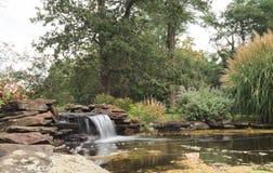 机器寿命和瀑布在池塘 库存图片