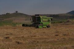 机器收割麦田,拾起五谷和做秸杆 免版税库存照片