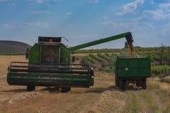 机器收割麦田,拾起五谷和做秸杆 免版税库存图片