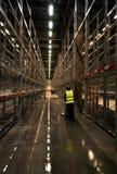 工作者洗刷的地板在空的仓库里 免版税库存照片