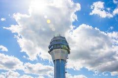 机场交通控制塔有天空的背景和云彩太阳发光强光 免版税库存照片