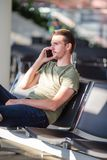 机场休息室等待的飞行航空器的乘客 有手机的年轻人在机场等待的着陆 免版税库存图片
