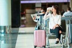 机场休息室饮用的咖啡和等待的飞行航空器的航空公司乘客 有glasss的白种人妇女,如果 库存图片