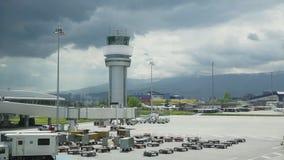 机场塔台 机场在全部容量的塔台 雷达与一架飞机的塔台横跨天空 股票录像