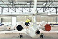 机场工作者检查一个航空器安全在飞机棚 免版税库存图片