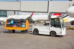 机场带着手提箱的行李台车在装载入航空器前 免版税库存图片