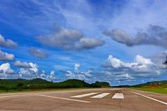 机场有空白线路、绿色山和蓝天的跑道出租汽车 免版税库存图片