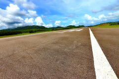 机场有空白线路、绿色山和蓝天的跑道出租汽车 库存图片