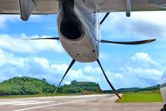 机场有空白线路、绿色山和蓝天的跑道出租汽车 免版税图库摄影