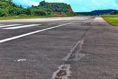 机场有空白线路、绿色山和蓝天的跑道出租汽车 库存照片